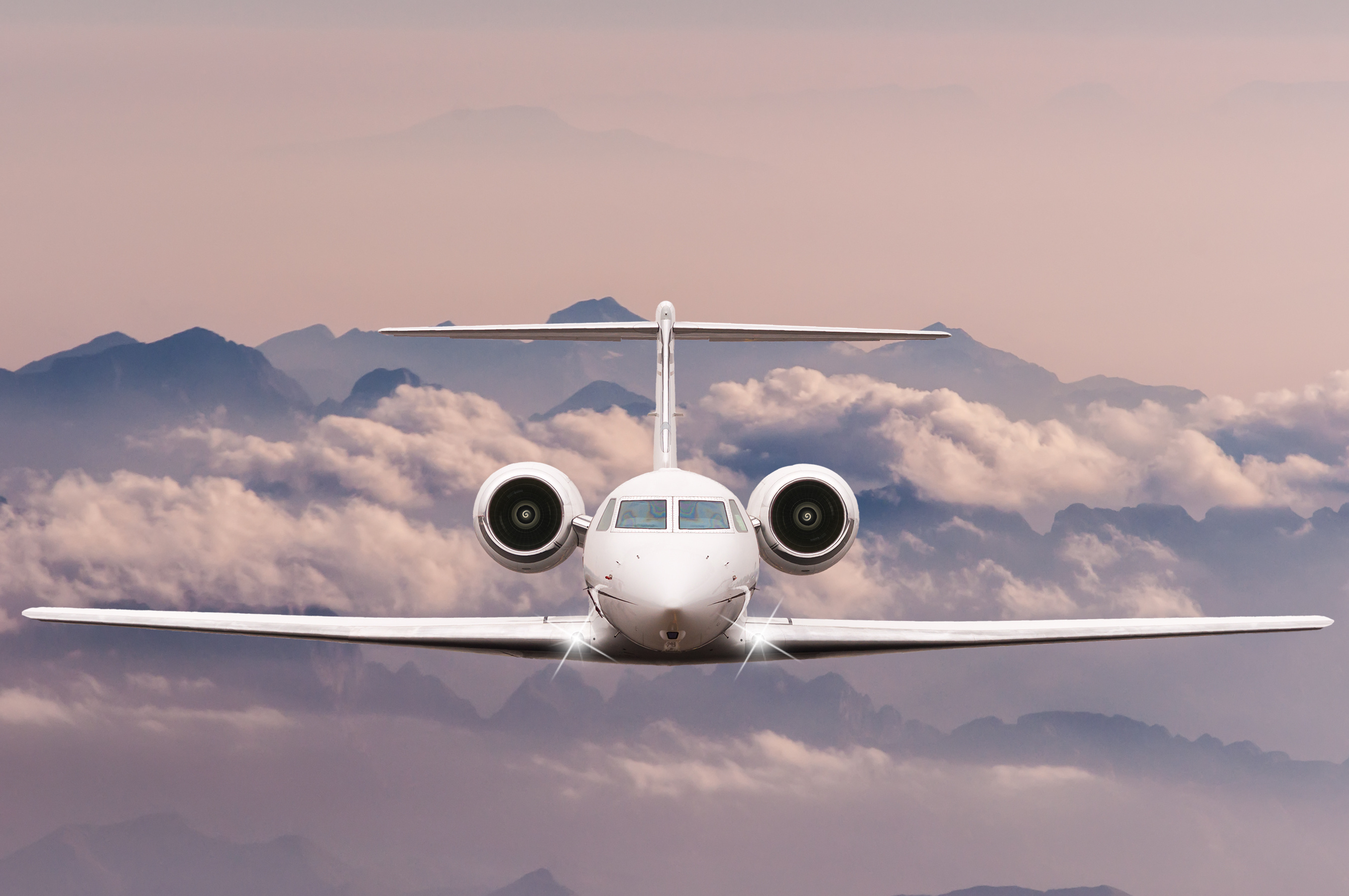 Travel concept. Front view of Jet airliner in flight with sky, cloud and mountain background. Commercial passenger or cargo aircraft, business jet fly over Alps.